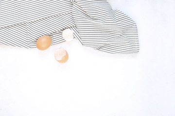Pastry cooking minimal concept - raw uncooked eggs on Crumpled Striped Napkin, concrete white background.