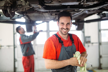Profecional car mechanic changing motor oil at maintenance repair service station