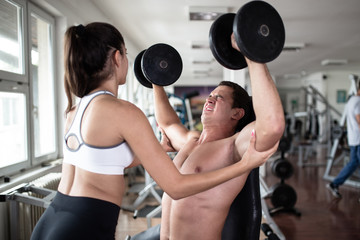 Young attractive adult man and woman exercising and doing weight lifting at fitness gym. Sport training indoors.