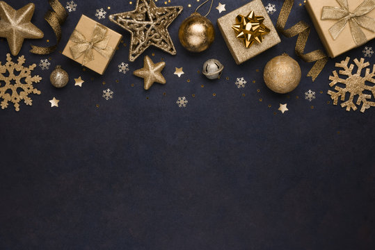 Golden snowflakes, gifts, christmas balls and stars on dark background