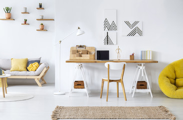 Real photo of a modern home office interior with graphics, desk, sofa and yellow pouf