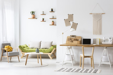 Simple home office with a desk and living room interior decorated with macrame and plants