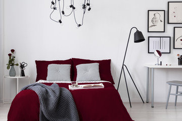 A burgundy bedding and gray pillows on a bed in a white wall bedroom interior. Real photo.