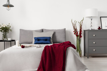 Glamour bedroom interior with a bed dressed in gray linen and cushions with contrasting accents of blue and red. Real photo.