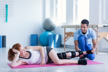 Woman with stiffener on the leg exercising during treatment with personal trainer