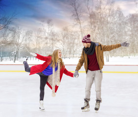 people, friendship, sport and leisure concept - happy couple holding hands on outdoor skating rink