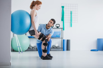 Woman with orthopedic problem exercising with ball while physiotherapist supporting her