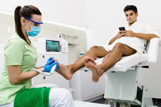 Young man having pedicure treatment in a modern beauty salon.