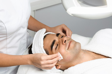 Male cosmetics. Good looking man receiving face treatment at luxury spa.