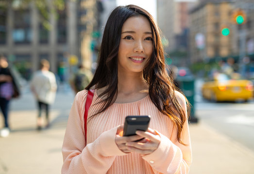 Asian woman in city walking using cell phone smile happy