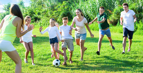 Parents with children gaily spending time together playing with ball outdoors