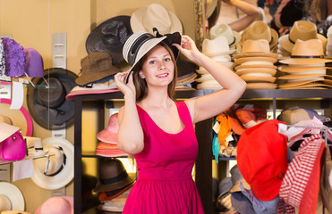 adult  woman try on hatinator hat  in shopping mall