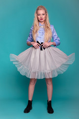 Blonde model in transparent dress and boots posing on blue background.