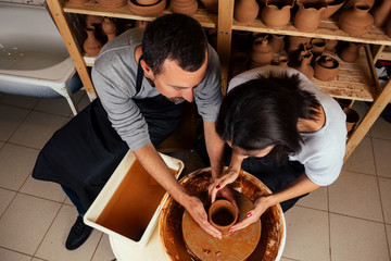 handsome man and happy woman couple in love working on potter wheel while at pottery workshop. husband and wife in the kraft creative studio,young family business shop sculpts pot from clay view top