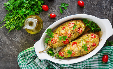 Minced meat chicken and vegetables stuffed eggplants on a grey background. Dinner food. Top view. Flat lay