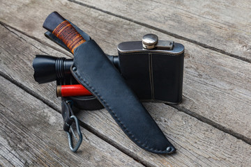A set of equipment for tourism and survival in the wild on a wooden background.