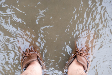 On a rainy day, the drain is not working,Brown shoes On the water flowing from the road,The concept of a trip is sometimes unexpected.