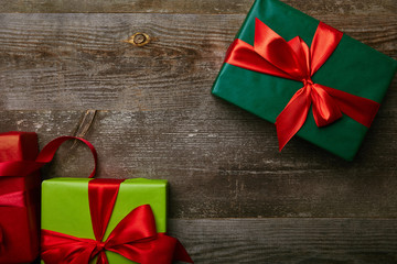 flat lay with wrapped festive presents with ribbons on wooden background