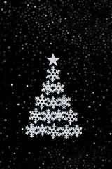 Christmas tree made of snowflakes on abstract blurred background with black glitter and bokeh light. Symbol of new year. Background, soft focus, abstract