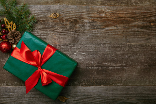 top view of wrapped green present with red ribbon and christmas toys on wooden background