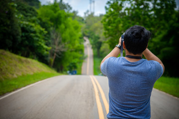 Photographer man taking photo with camera on Mountain Street. Traveler man standing on country road taking photo landscape beautiful location. Tourist man Travel concept