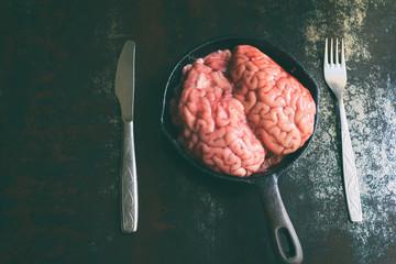 Pink brain before cooking on black metal frying pan. Raw meat. Offal