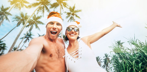Christmas image of Cheerful young people couple dressed red Santa hats making selfie with tropic palm trees background .