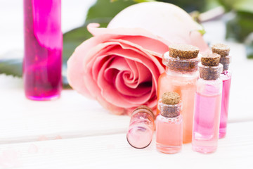 Spa and wellness setting with rose flower, sea salt, oil in a bottle on wooden white background