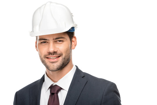 portrait of young male architect in hard hat looking at camera isolated on white