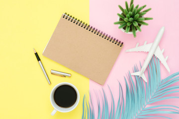 Flat lay design of travel summer concept - Top view mockup of blank paper notebook, pen, pastel leaf, coffee and plane on pink yellow pastel color screen. Travel in summer on pastel color background.