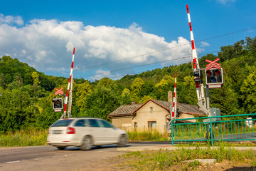 A white passenger car crossing a railroad crossing with barriers. Semaphores in front of the railway crossing. Warning signaling on railway in the Czech Republic. Car arriving at the railway crossing