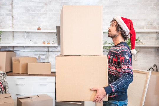 side view of young man in santa hat holding cardboard boxes during relocation