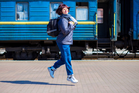 60 year old woman with backpack at railway station. Travel concept