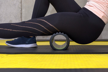 Close up view of woman exercising with foam roller