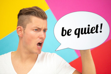 blond man holding a speech bubble with the words Be Quiet