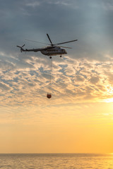 A fire helicopter collects water into the sea and flies toward the mountains to extinguish a forest fire on the background of a beautiful dawn sky. Rescue operation. Forest Fire Prevention