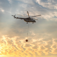 A fire fighter helicopter with a full basket of water flies against a beautiful sunset sky. Rescue operation. Forest Fire Prevention