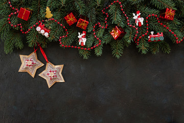 Christmas background with fir tree branches, Christmas decoration – stars, balls, trumpets, garland. Top view, close up