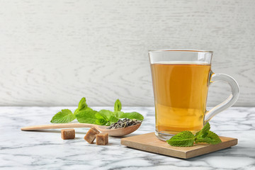 Cup of hot aromatic mint tea and spoon with dry leaves on marble table