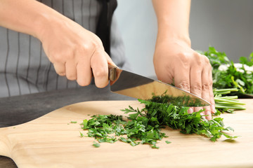 Woman cutting fresh green parsley on wooden board, closeup