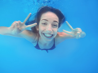 Beautiful young woman swimming in pool, underwater view