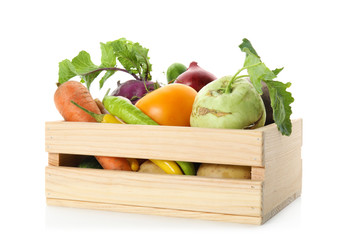 Fresh ripe vegetables in wooden crate on white background