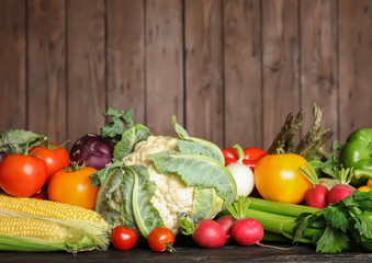 Assortment of fresh vegetables on table against wooden background. Space for text