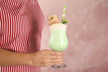 Woman with glass of delicious milk shake on color background, closeup. Space for text
