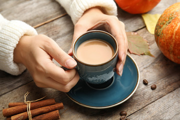 Woman holding cup with pumpkin spice latte on wooden table