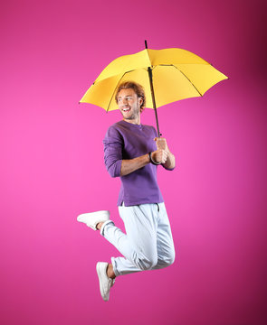 Man with yellow umbrella near color wall