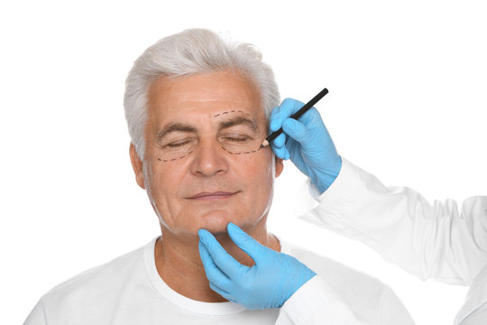 Doctor marking senior man face before cosmetic surgery on white background
