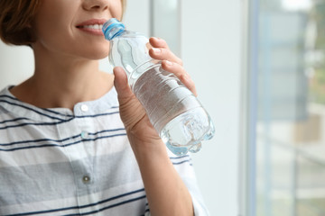 Woman drinking clean water from bottle at home, closeup. Space for text