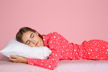 Beautiful teen girl sleeping with comfortable pillow on bed against color background