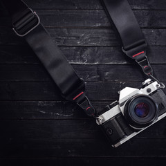 Classic camera on film with a strap. Wood black table background. Low-key light. Space for text